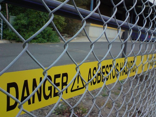 Yellow tape reads 'Danger! Asbestos Hazard' behind chain link fence