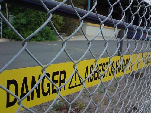 Yellow tape reads 'Danger! Asbestos Hazard' behind chain link fence